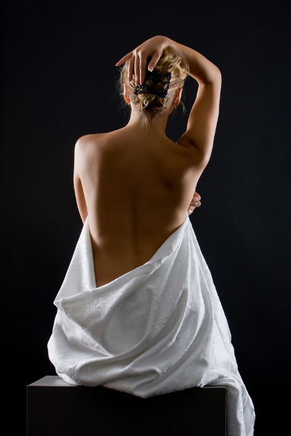 Photo of a woman's back with lower half wrapped in a sheet